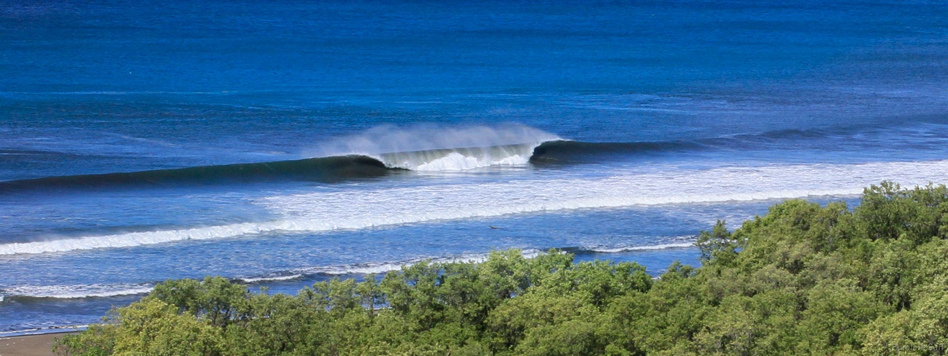 Aerial photograph of an offshore peeling a-frame wave found in Nosara, Costa Rica; one of the locations where Pureline Surf offers customized private surf lessons.