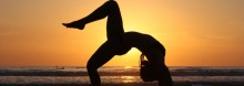A yogi preparing for a surf by doing a modified wheel pose in front of the Guiones beach sunset.