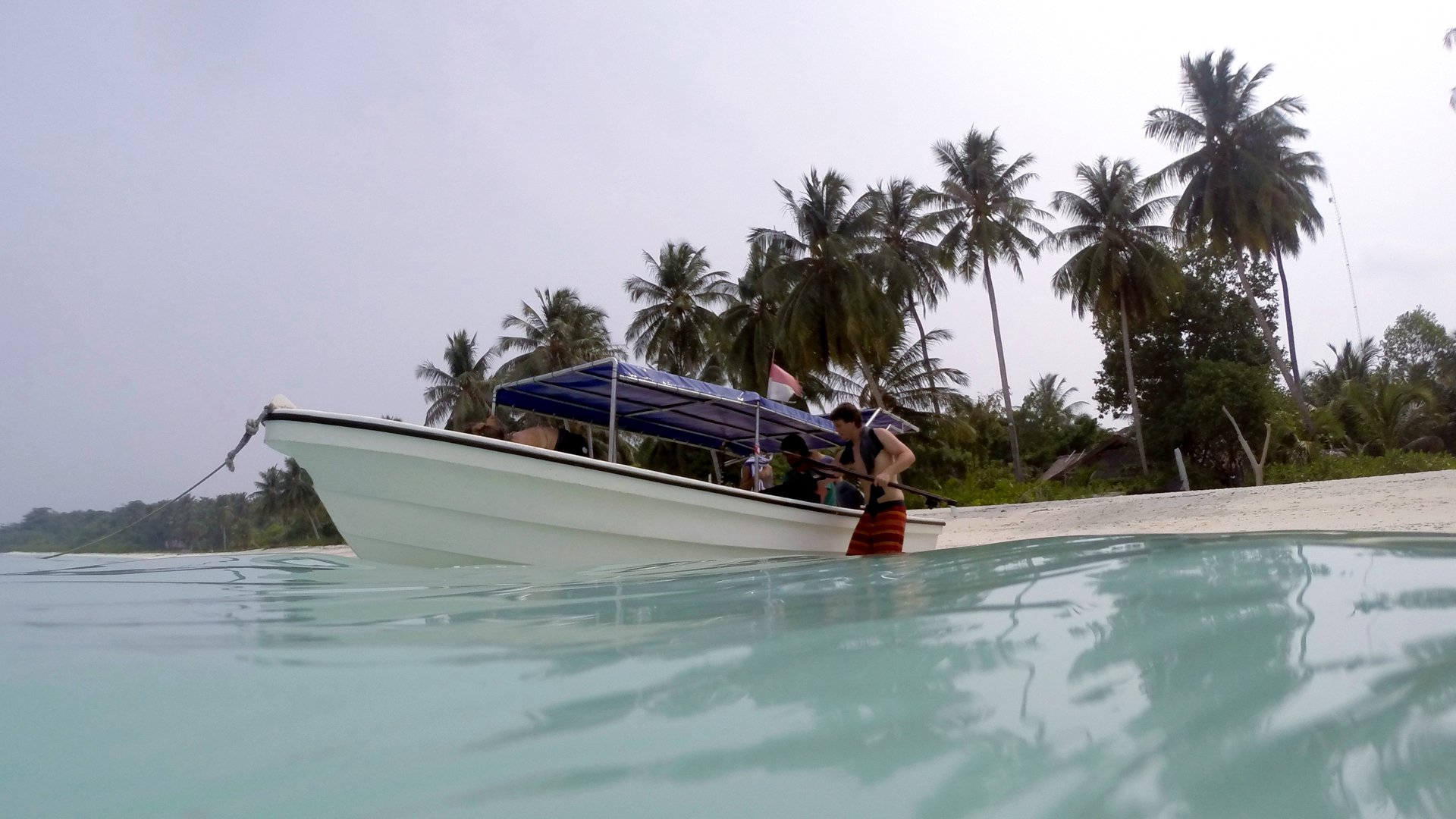 An in-water photograph of a small boat used to take Pureline's surfers out to the reef breaks in Indonesia.
