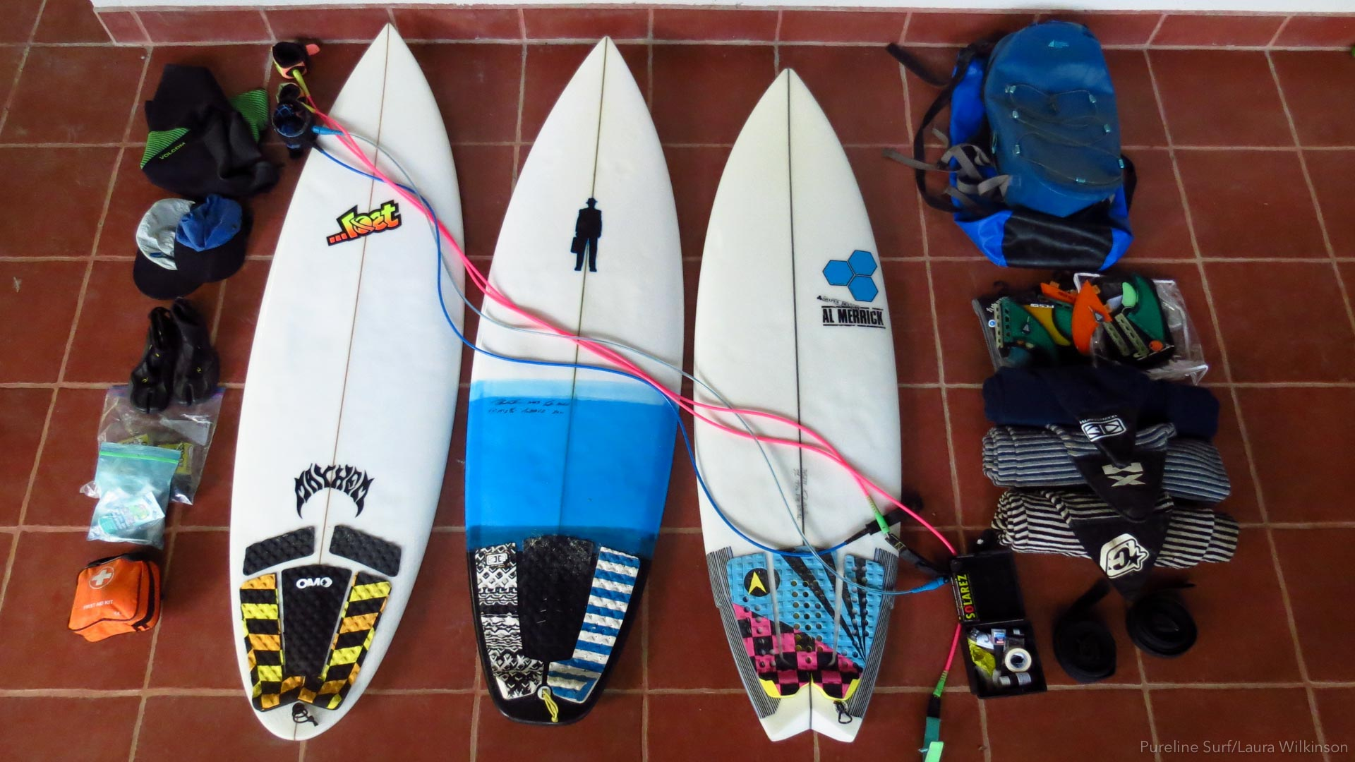Three shortboards laid out with fins, leashes, and other items used on surf trips with Pureline Surf.