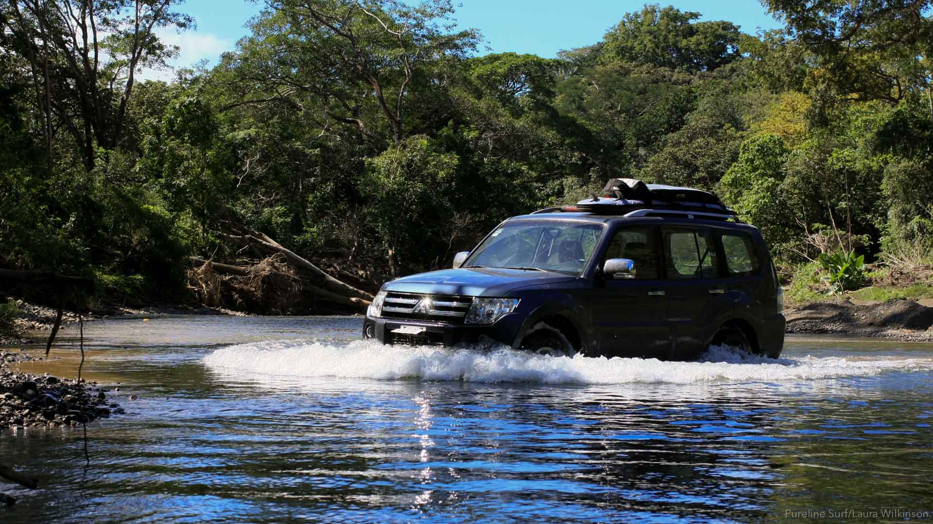 4x4 truck with surfboards on the roof, driving through a river in Costa Rica on the way to the best surf with Pureline.