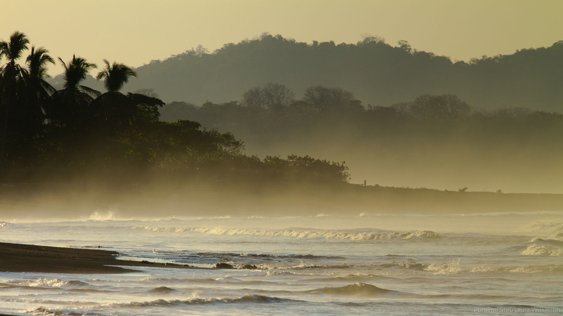 Misty view of the hills of Costa Rica with the ocean in the foreground, Ostional Beach, a Pureline Surf coaching location.