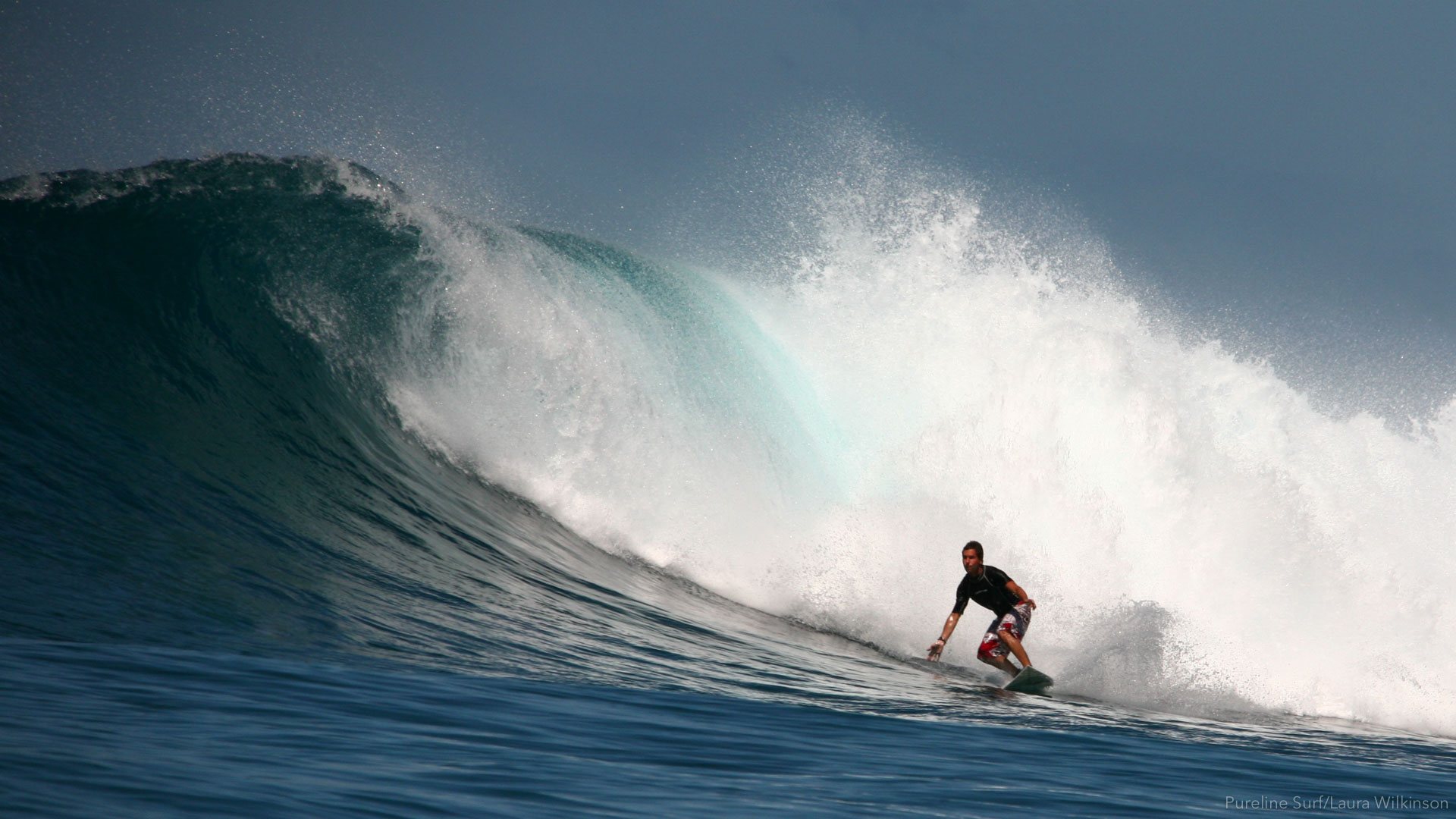 A Pureline surfer performing a forehand bottom turn on a triple overhead wave in Fiji, one of Pureline Surf's coaching destinations.