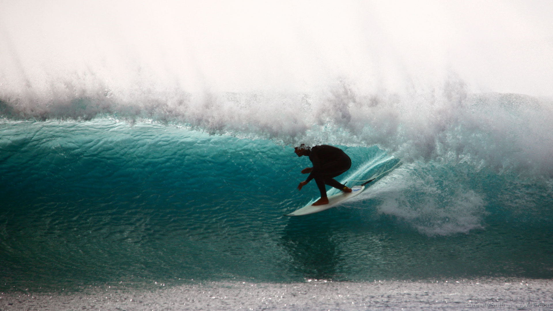 A Pureline surfer pulling into a backlight barrel in Fuerteventura, a Pureline Surf coaching destination.