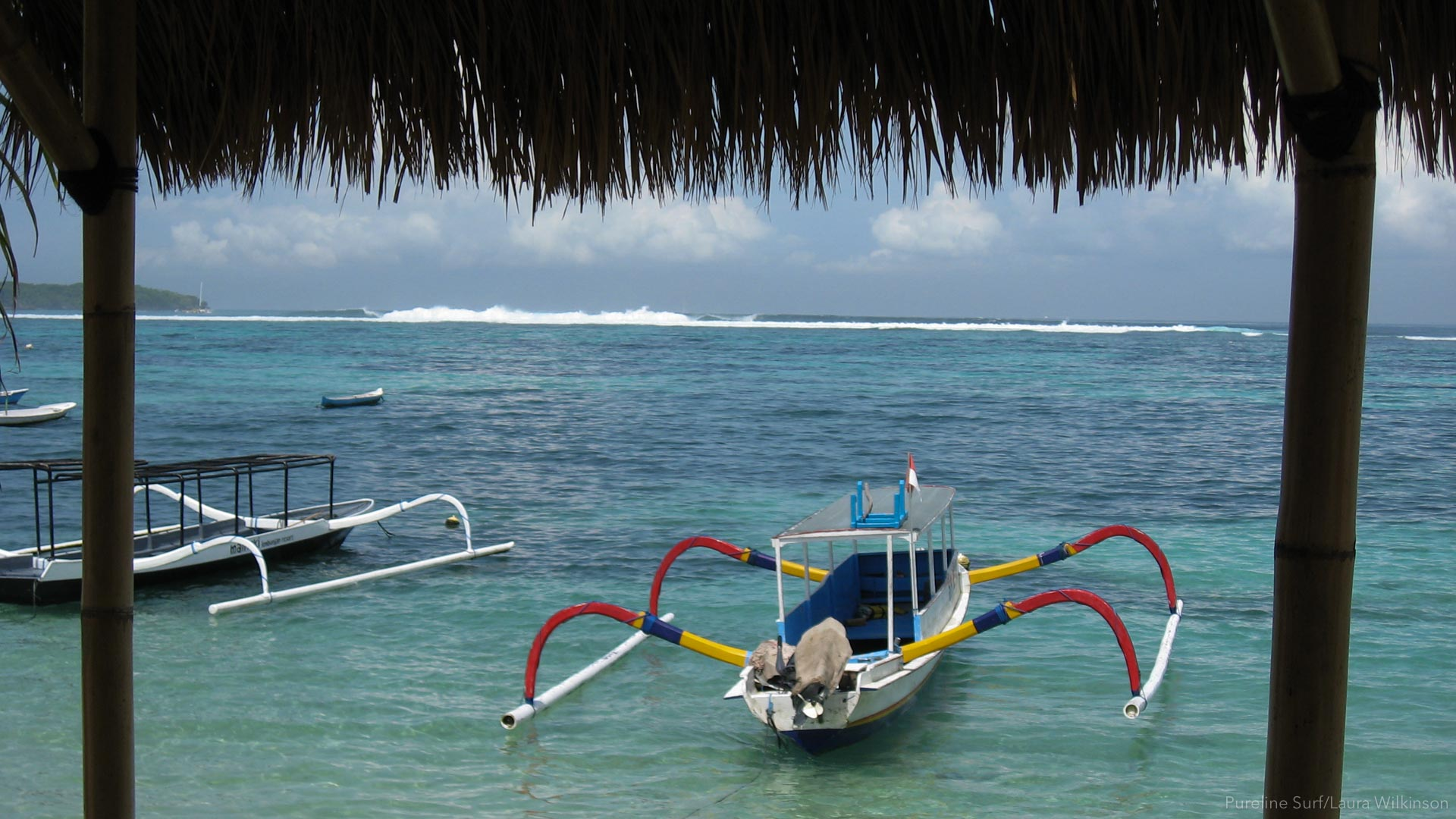 Boats in the foreground, waves in the background. A slice of life in Nusa Lembongan during a Pureline Surf Worldwide Coaching Trip.