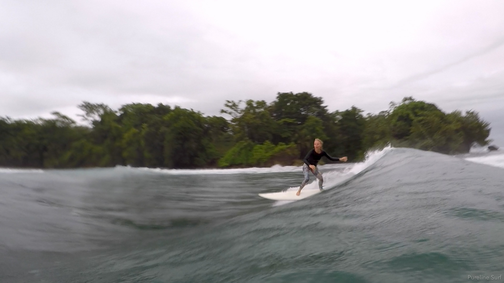 A Go Pro photo of a client surfing a perfect left over coral during a strike mission trip with Pureline Surf Coaching.