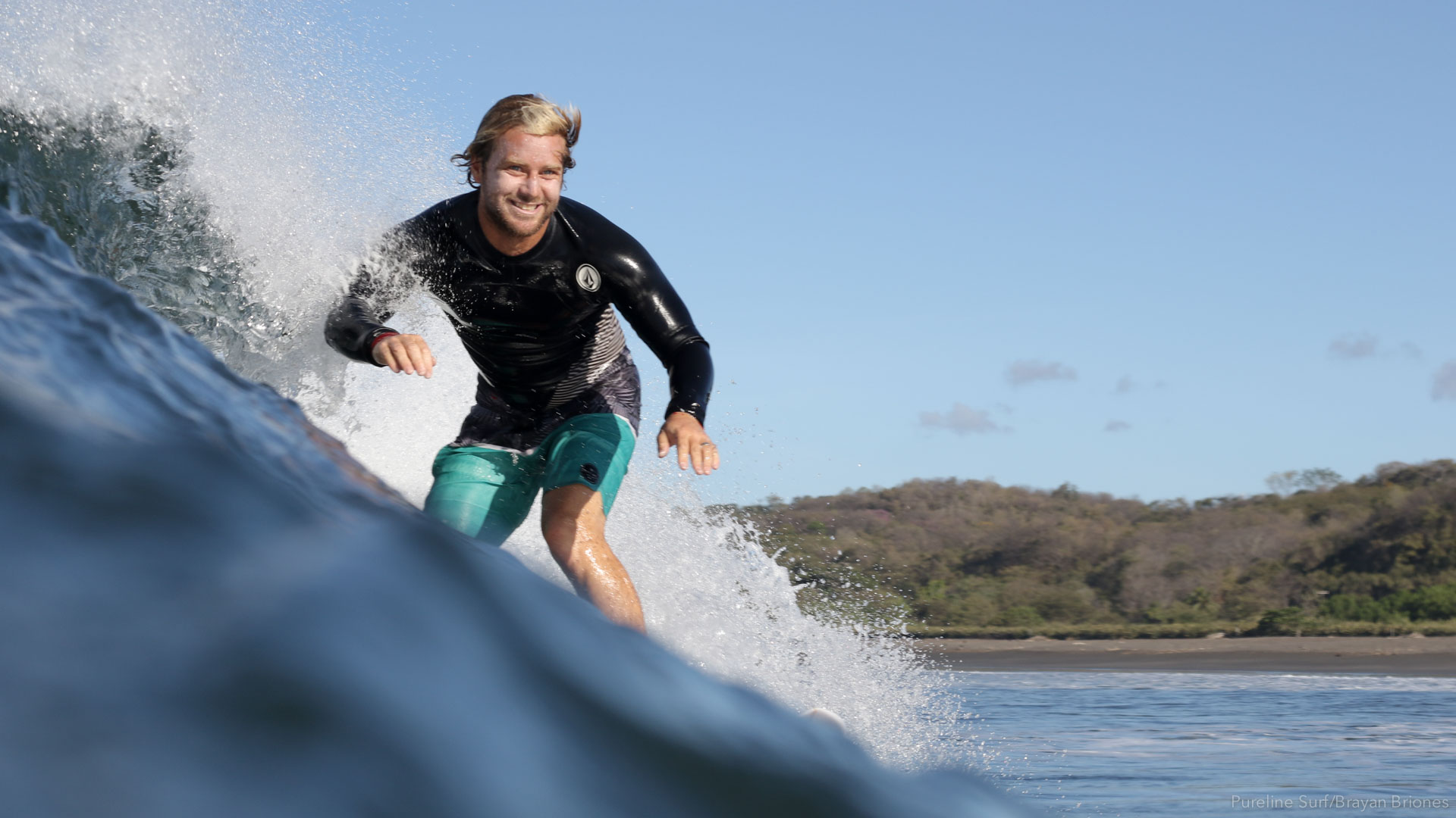 Pureline Surf's coach, Alex smiling as he surfs down the line in Costa Rica.