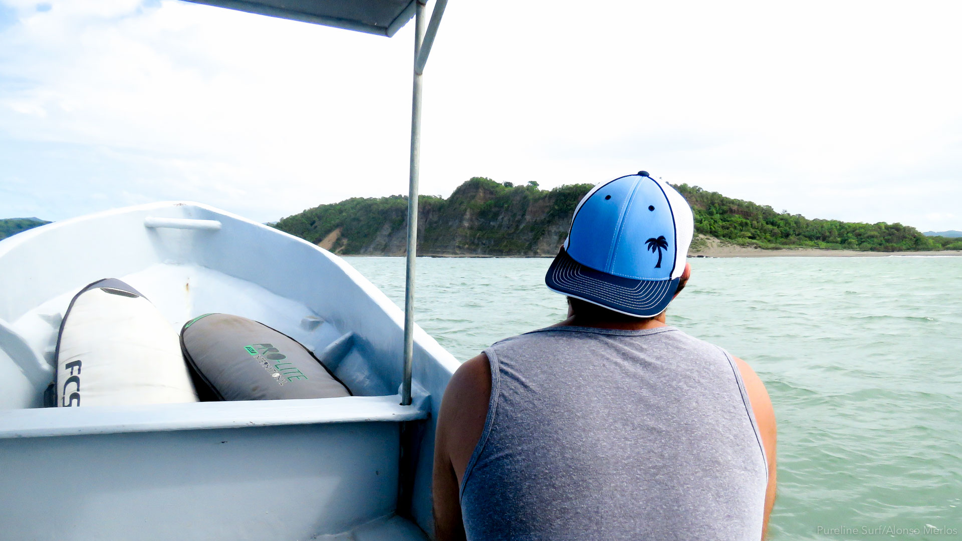 A pureline surf client looking out over the ocean from a boat filled with surf boards during a Pureline Surf Trip.