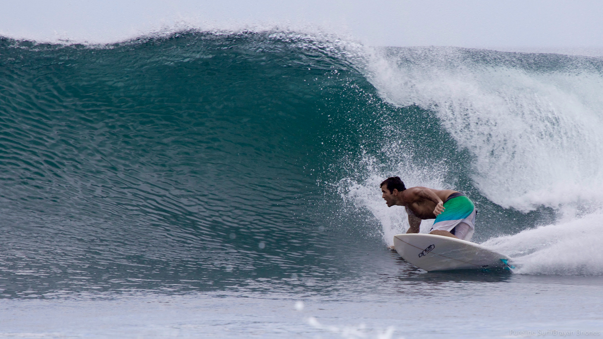 A Pureline surfer performing a bottom turn at a right hand beach break in Costa Rica, a Pureline Surf coaching destination.