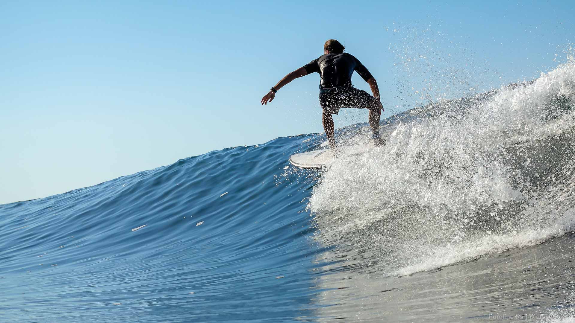 A Pureline Surf Coaching client taking a high line on a perfect wave during a private session.