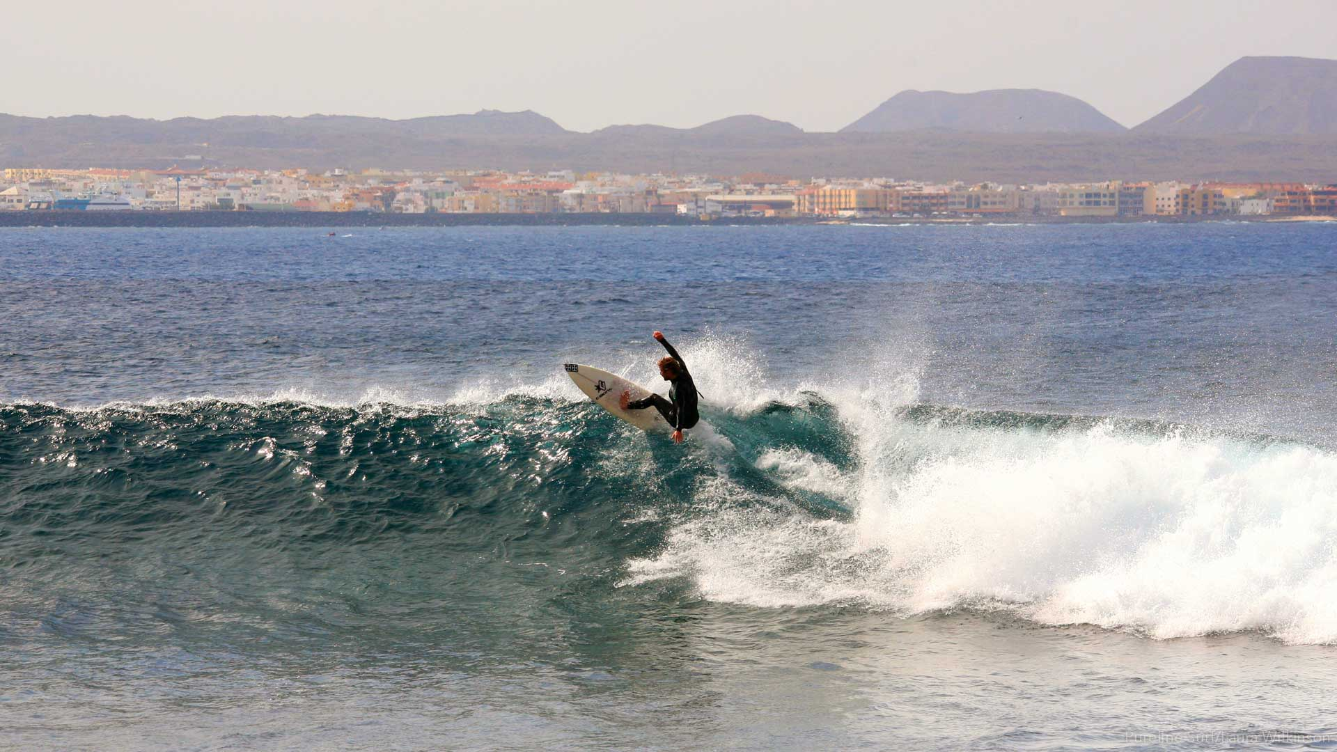 A Pureline surfer performing a forehand re-entry at Lobos point break in the Canary Islands with the town of Corralejo in the background.