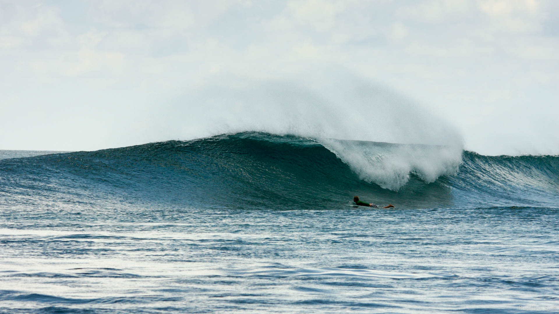 A peeling right-hand reef break in the Maldives with one surfer paddling out, a Pureline Surf coaching destination.