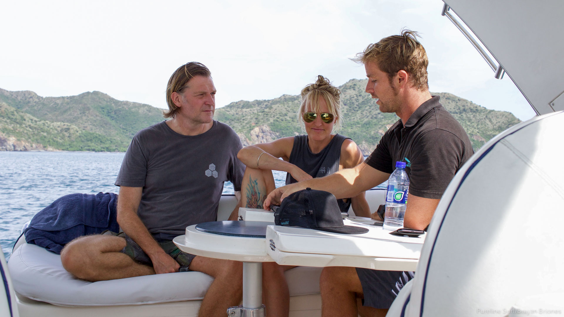 Pureline Surf's coach, Alex running through surf knowledge with two private clients on a private boat in Costa Rica.