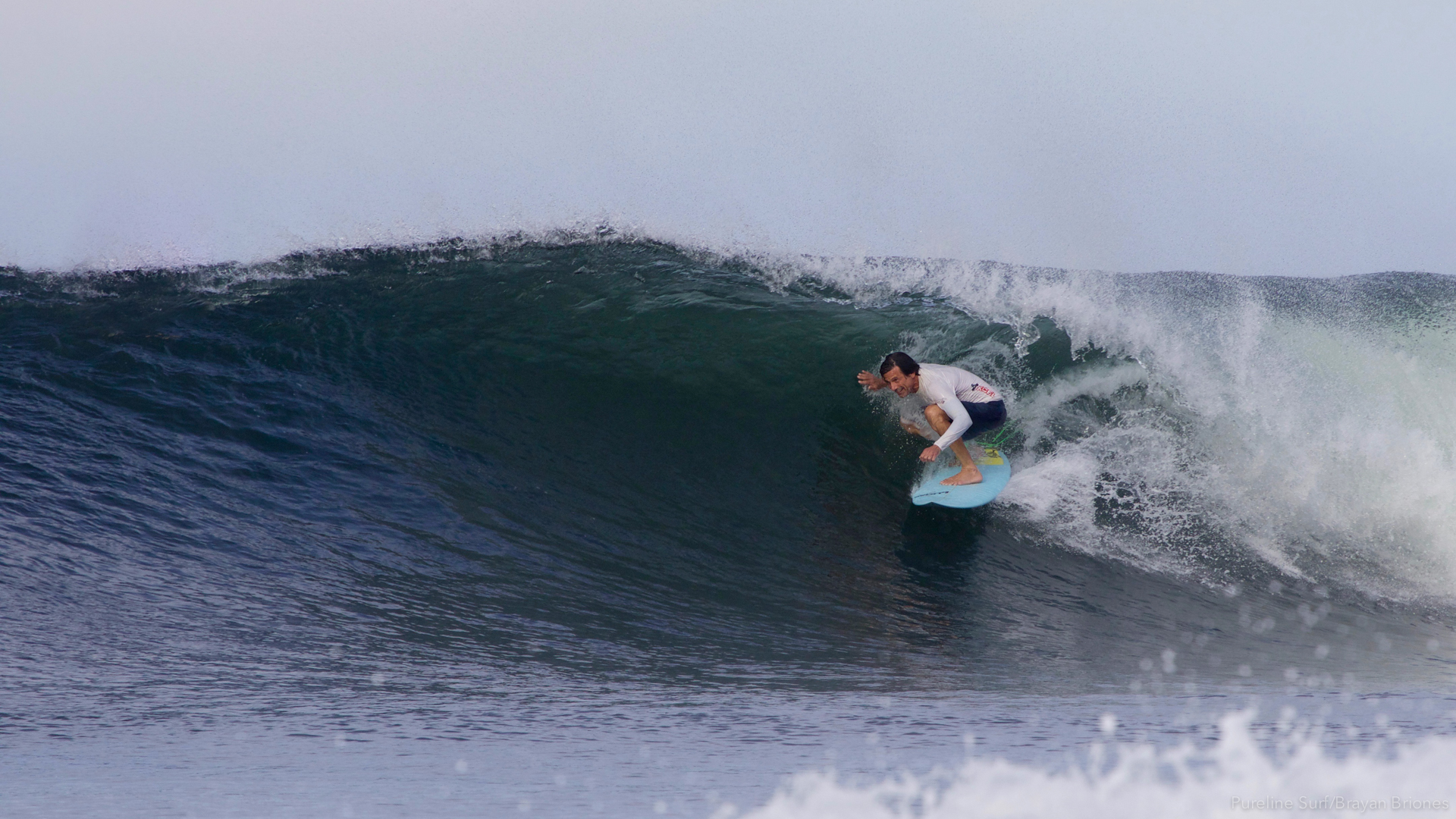 A surfer inside the barrel of a right hand beach break in Costa Rica, a Pureline Surf coaching destination.